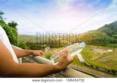Hand holding water bottle and background of nature view.