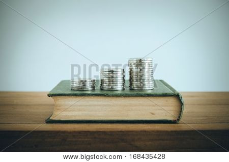 Business Growth Concept, Coin Stacks On Old Book. Vintage Filter.