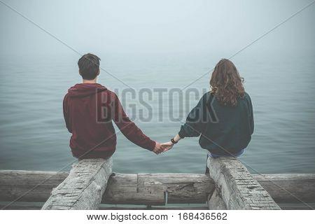 Lovers yong man and yong woman watching at Baikal lake