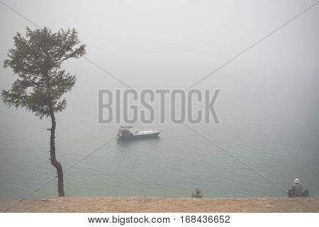 Old Man Wathing At Lonely Boat On Lake Baikal Under The Fog