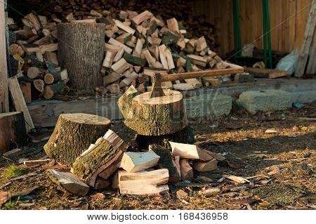 Axe in block on firewood just chopped background. Background of dry chopped firewood logs in a pile