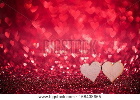 Two wooden hearts on red glowing bokeh hearts background for Valentines day