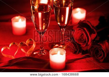 Valentines day celebration, glasses of champagne, candles, roses and hearts on red silk