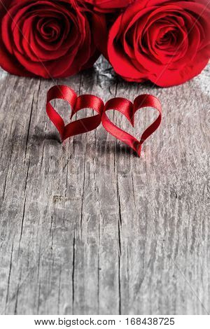 Two roses and ribbon hearts on wooden background, Valentines day