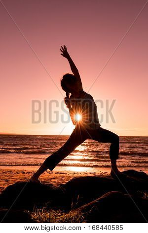 woman silhouetted practicing yoga on a maui beach at sunset