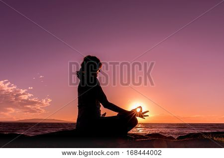 a woman meditating silhouetted on a maui beach at sunset