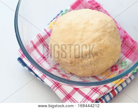 Cooking process. Preparing dough for cakes, pastries, buns or pizza. Leavened dough in transparent bowl. Close up image.