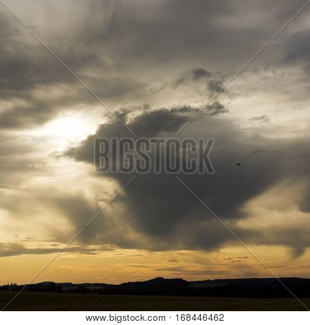 The landscape with cloudy sky and silhouette of light aircraft