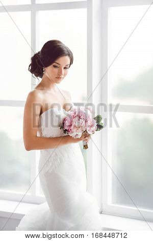 Beautiful bride. Wedding hairstyle make-up luxury fashion dress and bouquet of flowers. Young attractive multi-racial Asian Caucasian model like a bride against white room with big window tender looking down . Side view