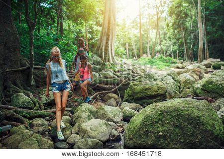 European tourists hiking through jungle in Thailand shot with lens flare