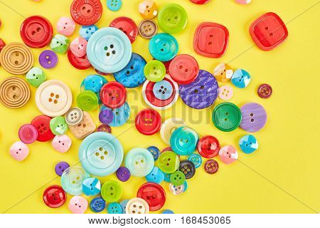 Colored sewing buttons on yellow paper background.