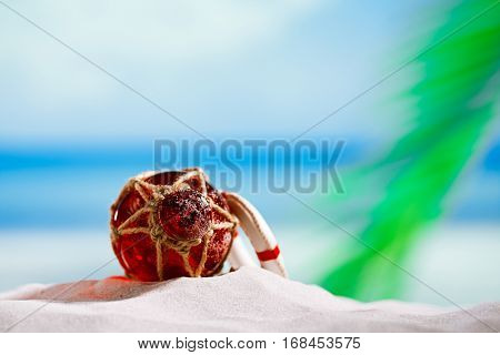 red Glass float on beach sand and sea blue background