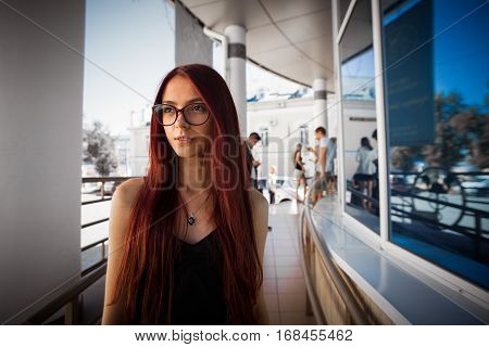 Urban city portrait of girl. Beautiful thinking girl with long red hair and glasses looking aside. Pretty girl in black dress on city, beautiful architecture background. Picture of pretty urban girl