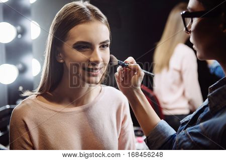 Face makeup. Charming delighted young woman sitting and smiling while having powder applied on her face by a professional makeup artist