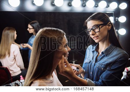 Healthy skin blush. Pleasant pretty professional visagiste looking at her client and applying blush while putting on makeup