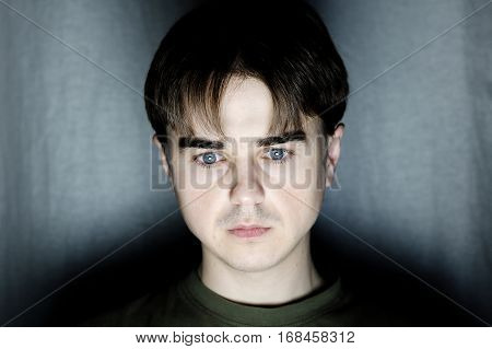 young man portrait face in dark room at dark background, handsome youngster serious face programmer coding at night hacking, working, Internet addiction idea