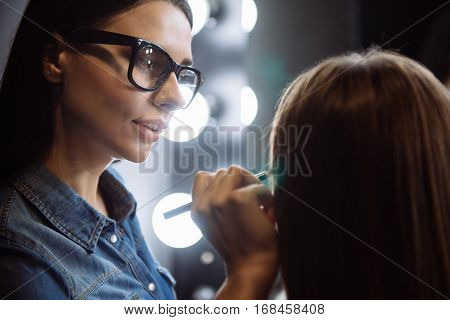 Beautiful eyes. Pleasant nice professional makeup artist holding a cosmetic pencil and drawing with it while working with a model