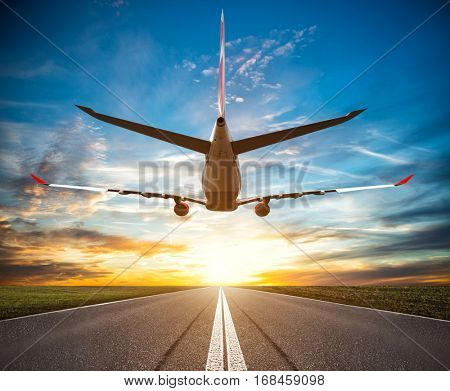 Passenger plane fly up over take-off runway at sunset. Dramatic sky on background. Travel concept