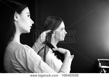 Long straight hair. Good looking professional female hairdresser holding a hair straightener and straightening hair of the model while making a hairstyle for her