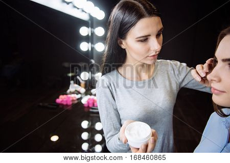 Skincare products. Attractive beautiful young woman holding a bottle of cream and applying some cream on her clients cheek while using skincare products