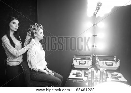 Beautiful curls. Good looking nice skillful hairdresser using hair curler and putting them on her clients hair while making a hairstyle for her