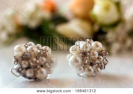 Luxury Pearl Earings With Stone On Background Of Boutonnieres With Roses For Gorgeous Wedding Ceremo