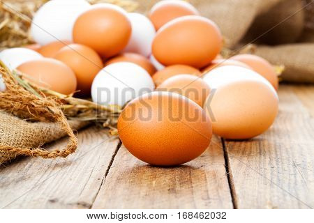 brown and white eggs on old wooden background