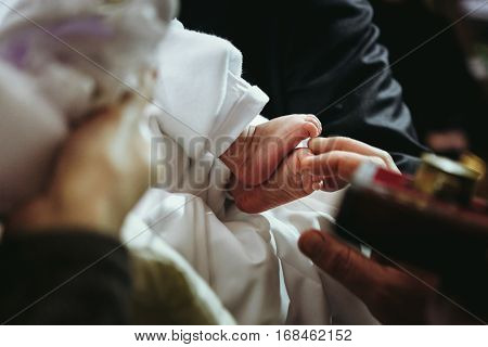 Christening Of Little Baby In Church, Close-up Feet And Priest Hand