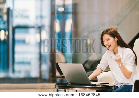 Beautiful Asian girl celebrate with laptop success pose education or technology or startup business concept with copy space
