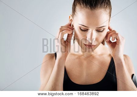 Sound of dream. Concentrated pretty active woman listening to music after having training and using headphones.