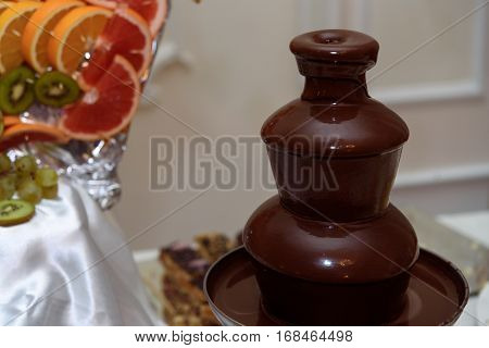 delicious chocolate fountain fondue at candy bar at luxury wedding reception