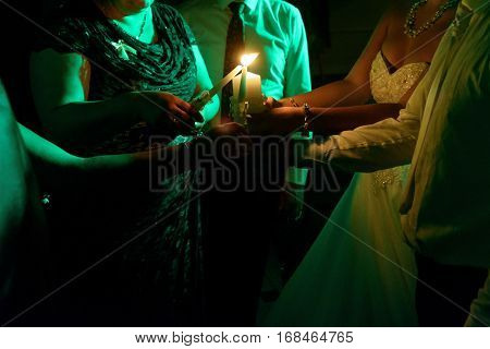 happy bride and groom getting candle light from their family