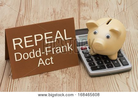 The Dodd-Frank Act A golden piggy bank card and calculator on a wood desk with text Repeal Dodd-Frank Act