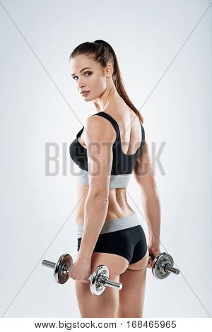 Well built. Beautiful young athletic girl posing with dumbbells after exercising and demonstrating her figure on a grey background.