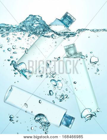Three bottles of thermal water, cosmetic moisturizing lotion under the water. Big wave on the surface of water and many big and small bubbles in the water. Gradient blue background