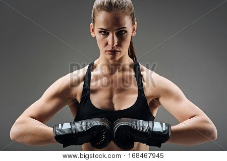 Non female hobby. Confident young active woman posing and standing on grey background while wearing boxing gloves.