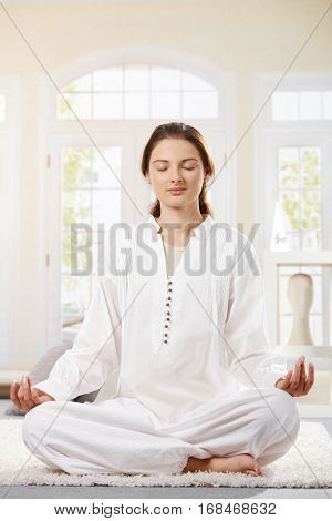 Young woman in white clothes sitting in lotus position, doing yoga, eyes closed, smiling.