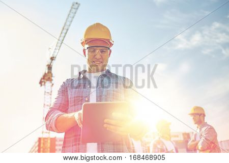 business, building, industry, technology and people concept - smiling builder in hardhat with tablet pc computer over group of builders at construction site poster