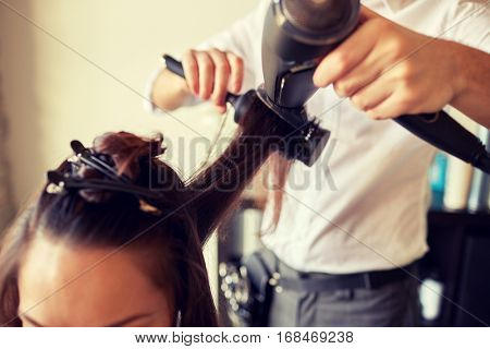 beauty, hairstyle, blow-dry and people concept - close up of young woman and hairdresser with fan and brush making hot styling at hair salon
