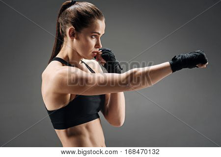 Kick it. Strong young pretty girl boxing while standing on a grey background and having training.