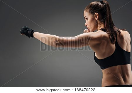 Good kick. Concentrated young pretty girl boxing while standing on a grey background and having training.