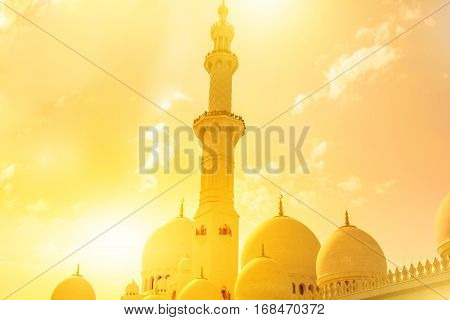 Details of domes and minaret of Sheikh Zayed Grand Mosque at sunset, Abu Dhabi, United Arab Emirates. Islamic culture concept. Muslim religious icon. Day light shot.