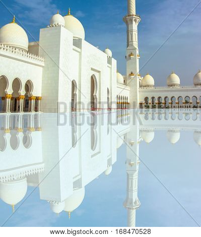 Sheikh Zayed Grand Mosque with minaret, domes and columns reflecting. The Sheikh Zayed Mosque is located in Abu Dhabi and is considered the most important place of worship in the country.