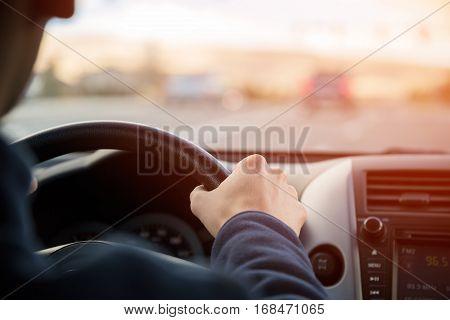 Man driving car, hands on steering wheel