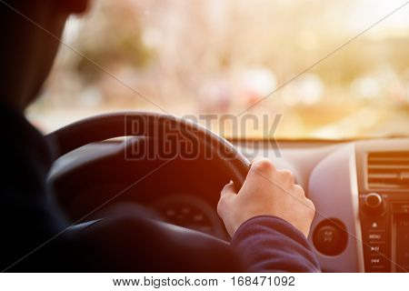 Man driving car, hands on steering wheel