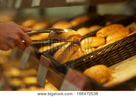 food, baking and sale concept - close up of hand with tongs taking bun at bakery or grocery store