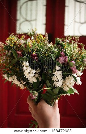 Beautiful White Flowers Bouquet In Hand  At Rustic Wooden Red Door, Simple Adorning