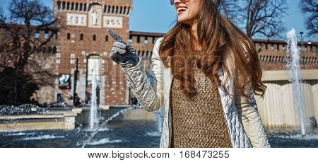 Tourist Woman Near Sforza Castle In Milan Pointing On Something