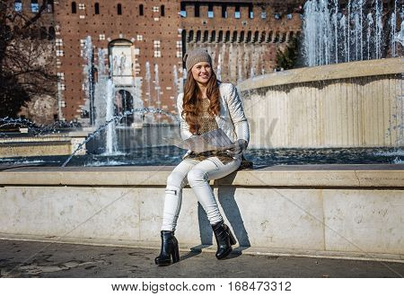 Rediscovering things everybody love in Milan. Full length portrait of smiling trendy woman near Sforza Castle in Milan Italy with map