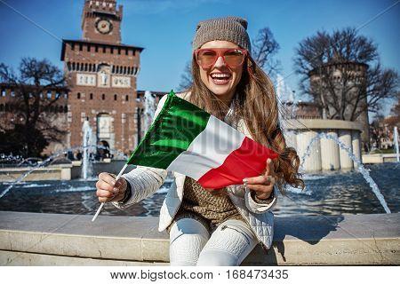 Tourist Woman Near Sforza Castle In Milan, Italy Showing Flag